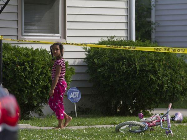 a young girl watches as police respond to a double homicide in Michigan.