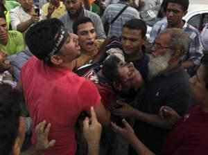 Supporters of Egypt's ousted President Mohammed Morsi carry an injured man to a field hospital following clashes with security forces at Nasr City.