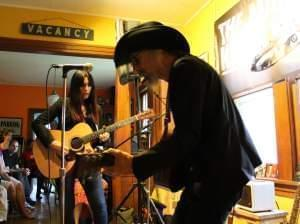 A man and a woman playing guitars in a living room.