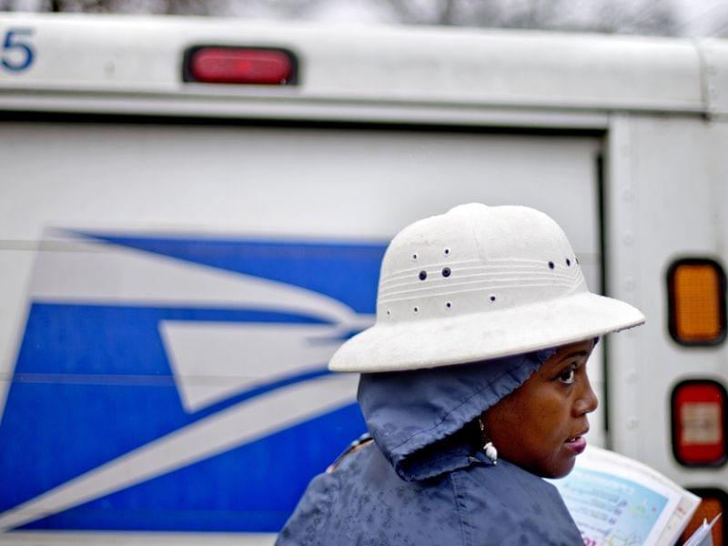 U.S. Postal Service letter carrier Jamesa Euler delivers mail in the rain in Atlanta in February.