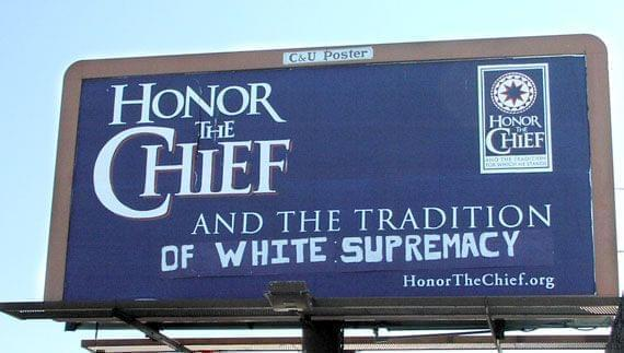 Defaced billboard saying Honor the Chief with graffiti changing the meaning
