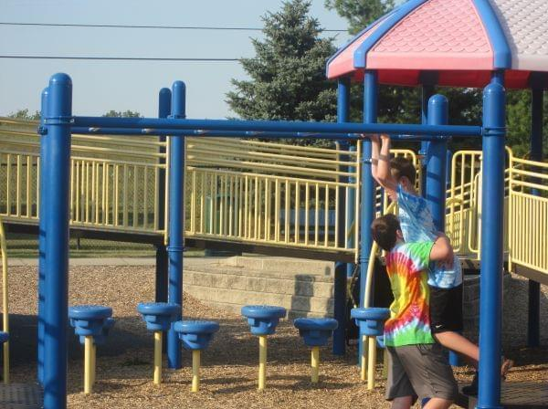 Alex Whiteman helps his brother Rylan, who has cerebral palsy, off the monkey bars at the Playground for Everyone in Danville, Ill.
