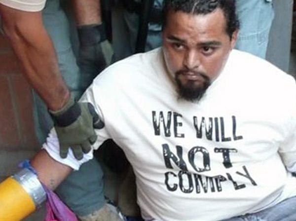 "protester wearing T-shirt with words ""We will not comply."""
