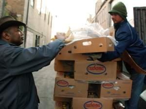Roger Gordon (left) is offered a box of bananas from a worker who was throwing away the lightly speckled fruit at Mexican Fruits in Washington, D.C. Gordon's startup, Food Cowboy, works with truckers to divert edible produce from landfills to fo