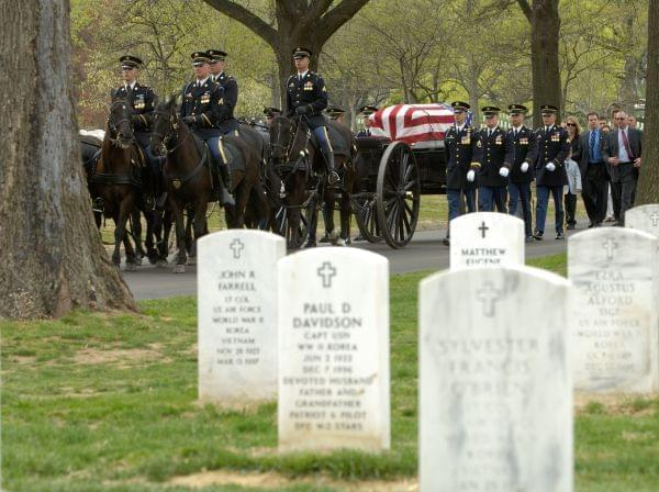 A horse-drawn caisson carries a casket and leads family members through Arlington National Cemetery.