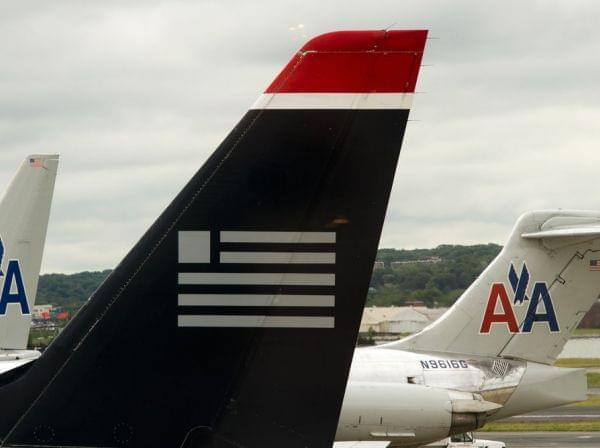 A US Airways plane rests near two American Airlines jets at Ronald Reagan Washington National Airport last year. The combined carrier would be named American Airlines.