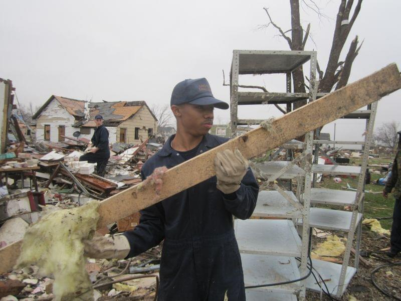 Chelorenz Watts, 19, helps clear debris from a home destroyed by the storm in Gifford, Ill.