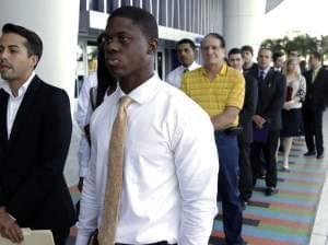 Luis Mendez, 23, left, and Maurice Mike, 23, wait in line at a job fair held by the Miami Marlins at Marlins Park in Miami on Oct. 23, 2013. The nation's unemployment rate slipped to 6.6 percent in January, but employers added only 113,000 jobs