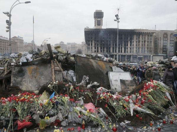 Flowers cover one of the barricades heading to Kiev's Independence Square, the epicenter of the country's recent unrest on a mourning day, Ukraine, Monday, Feb. 3, 2014. Official reports say 82 people were killed in severe clashes between o