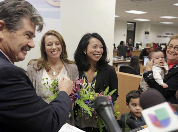 Cook County Clerk David Orr, left, performs a marriage ceremony for Theresa Volpe, second from left, and Mercedes Santos on Friday, Feb. 21, 2014, in Chicago.