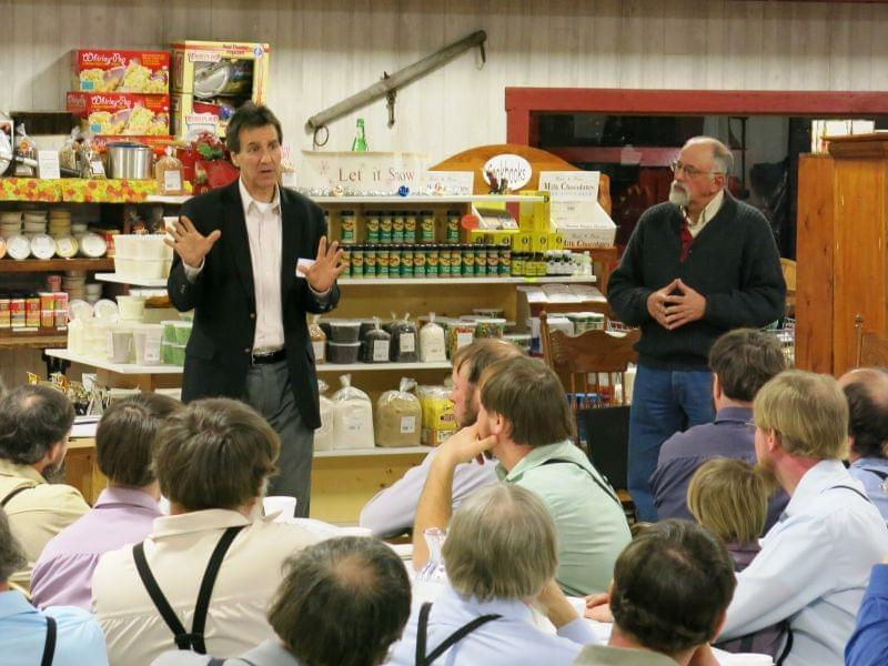 Michael Doherty with the Illinois Farm Bureau, left, speaks with a group of Amish farmers at a recent food hub education meeting. Standing next to him is organizer Dave Bishop.