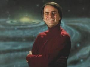 Carl Sagan standing in front of a spiral galaxy.