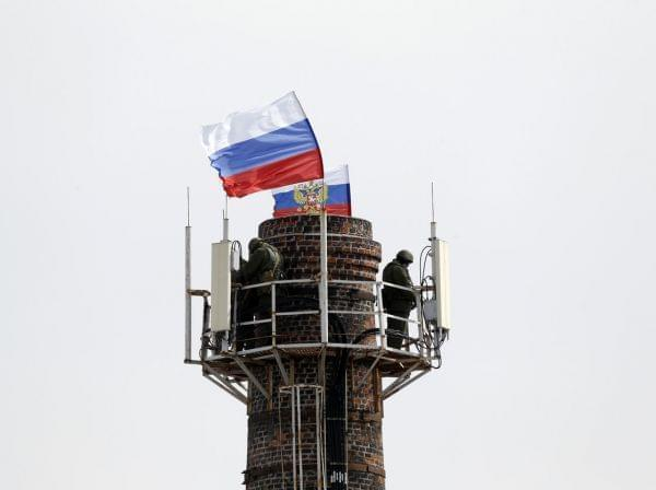 Armed men stood atop a chimney near Ukraine's naval headquarters in Sevastopol, Crimea, on Wednesday. They raised Russian flags after taking over much of the facility.