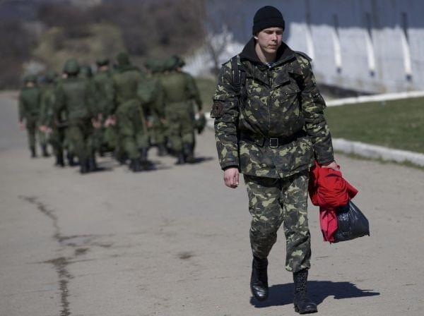 As Russian soldiers walked one way in the distance, a departing Ukrainian soldier carried some of his belongings Friday at a military base in Perevalne, Crimea.