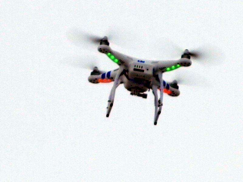 A remote-controlled quadcopter hovers over a Bloomington, Ill., parking lot, where Colby offered test flights of new unmanned vehicle models.