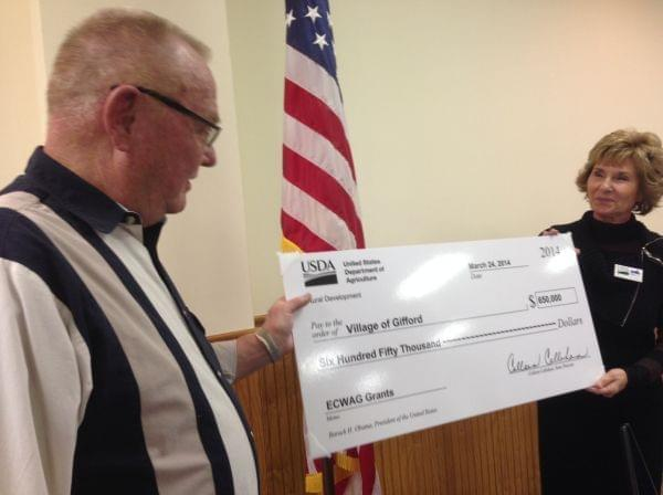 The USDA's Colleen Callahan present Gifford Mayor Derald Ackerman with a check to made needed improvements to the town's water plant and tower.