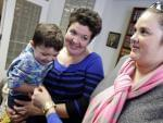 Nicole Yorksmith, left, holds her son while standing with her partner Pam Yorksmith. They were among four legally married couples who filed a federal civil rights lawsuit seeking to compel Ohio to recognize same-sex marriages on birth certificates.