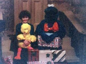 Paula Gray Havlik sits with David Thiel, who is dressed in a furry blue monster suit, on a replica of the Sesame Street steps.