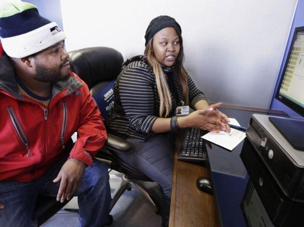 In this Nov. 8, 2013, photo, enrollment counselor Kenya Williams helps Jerome Davis Jr. 36, sign up for Medicaid at the Westside Health Authority in Chicago.