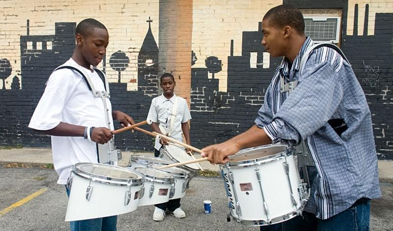 Three drummers drumming outside the Art Theatre