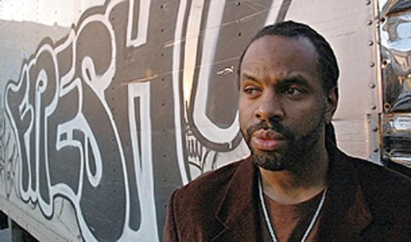 Byron Hurt standing by graffiti covered wall