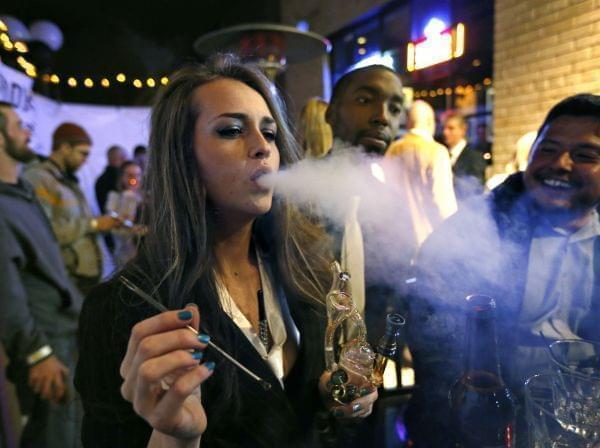 In this Dec. 31, 2013, file photo, partygoers smoke marijuana during a Prohibition-era themed New Year's Eve party at a bar in Denver, celebrating the start of retail pot sales.