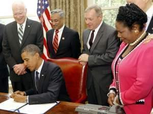 President Obama signs the Fair Sentencing Act in 2010, as Attorney General Eric Holder and a bipartisan group of senators look on.
