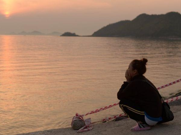 As the sun set Wednesday in Jindo, South Korea, a woman kept watch on the waters where the Sewol ferry sank. It's feared the death toll will reach 300.