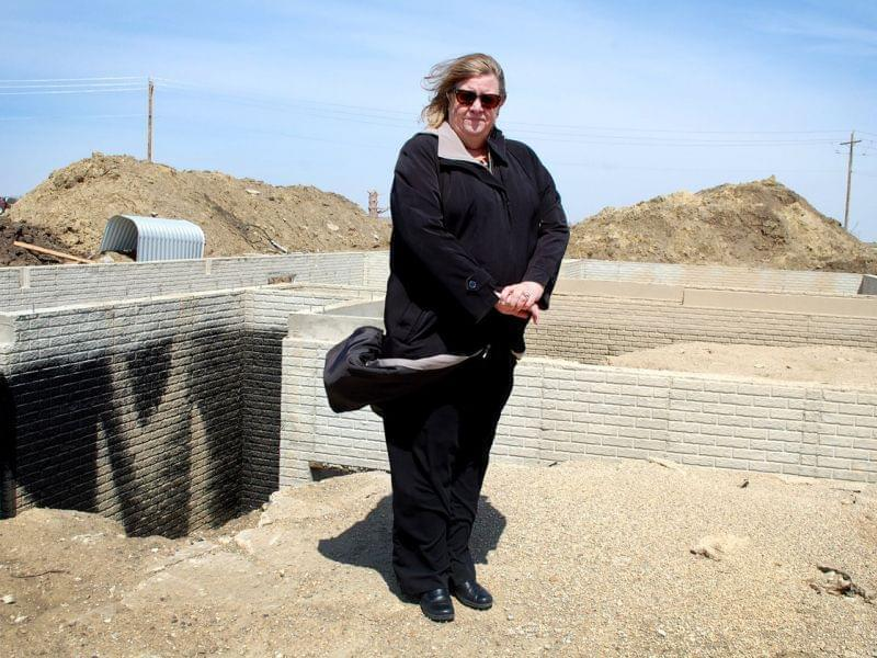 Lorelei Cox stands where her yard used to be. Having faced a tornado and a