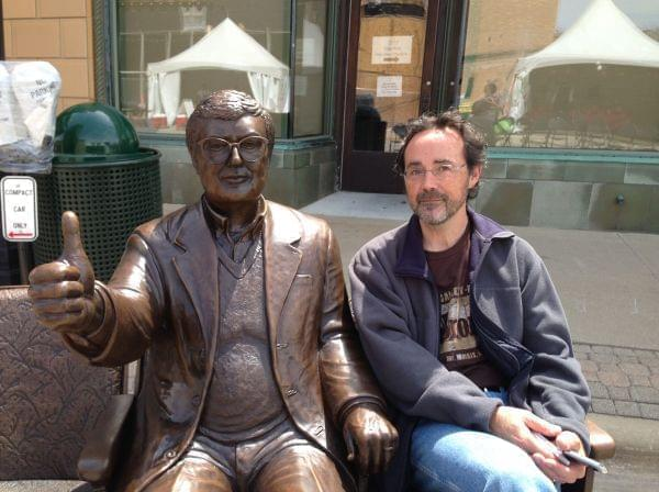 Artist Rick Harney poses next to his bronze sculpture of Roger Ebert on April 24, 2014 in Champaign, Ill.