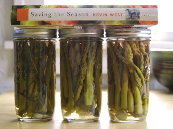 Three jars of pickled asparagus with a cookbook