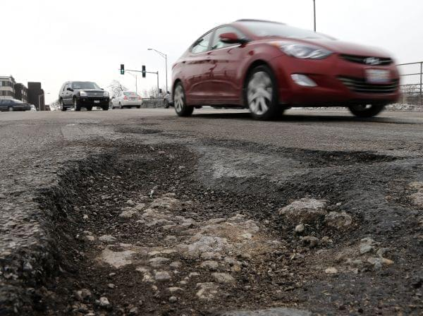 Motorists on Wednesday, Feb. 12, 2014 travel in Chicago, dodging potholes as the effects of a harsh winter challenge the city's infrastructure .