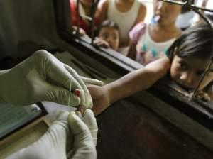 A health official takes a blood sample from a child's finger for a malaria test at a clinic in Bong Ti Lang village on the Thai-Myanmar border.