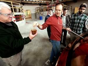 John Stuart (left) of Green Man Brewery grabs a Tater Ridge mash sample from Sierra Nevada's Scott Jennings (center) at the Sierra Nevada brewery in Mills River, N.C.