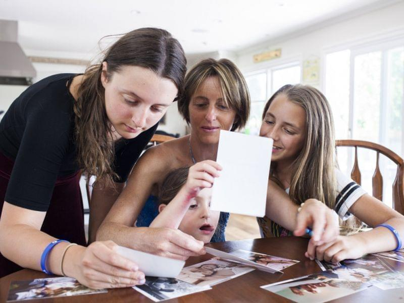 Melissa Sherak Glasser (center) looks at family photos with daughters Gabriella, 14, Lily, 5, and Maya, 11, at home in Woodland Hills, Calif.