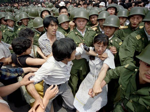 A young woman is caught between civilians and Chinese soldiers, who were trying to remove her from an assembly near the Great Hall of the People in Beijing, June 3, 1989. Pro-democracy protesters had been occupying Tiananmen Square for weeks.