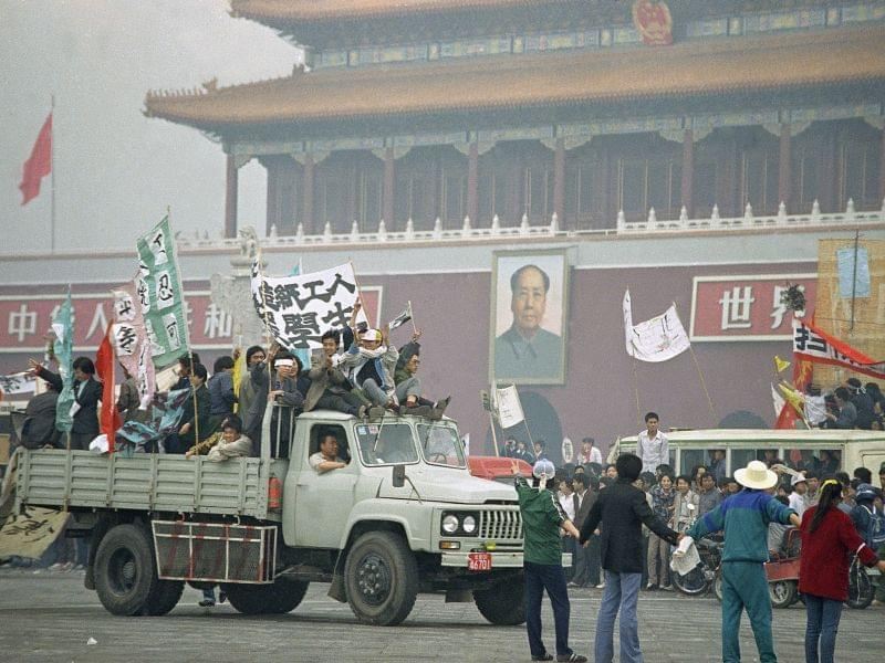 Demonstrators parade past the Gate of Heavenly Peace and the portrait of Mao Tse-Tung, toward rally in Tiananmen Square of striking students, Thursday, May 18, 1989, Beijing, China.