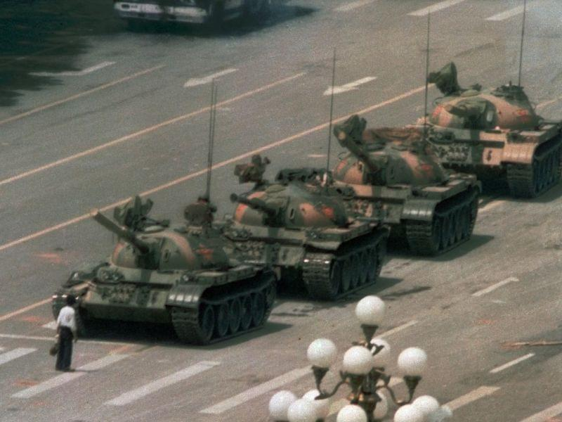 A Chinese man stands alone to block a line of tanks heading east on Beijing's Cangan Blvd. in Tiananmen Square on June 5, 1989. The man, calling for an end to the recent violence and bloodshed against pro-democracy demonstrators, was pulled away by bystanders, and the tanks continued on their way.