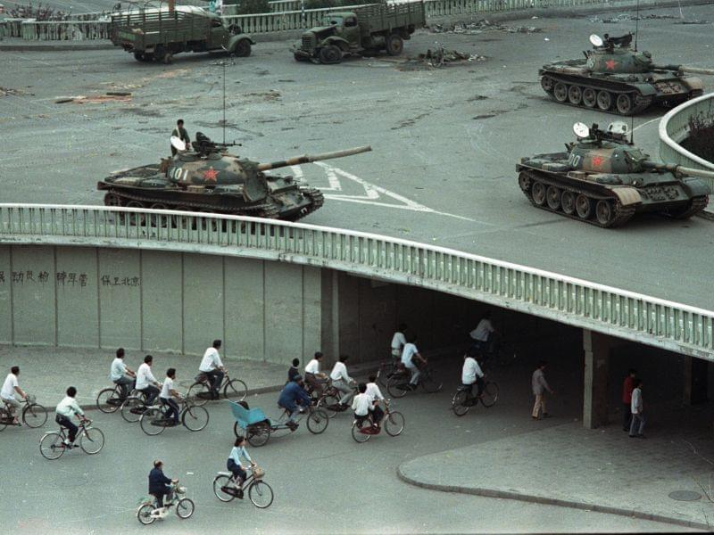 Bicycle commuters, sparse in numbers, pass through a tunnel as above on the overpass military tanks are positioned in Beijing, China, two days after the Tiananmen Square massacre,on Tuesday morning, June 6, 1989. The slogan on the wall at left reads,