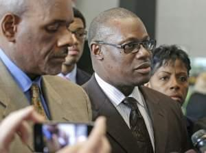 Illinois state Rep. Derrick Smith, center, speaks to reporters at the federal building Tuesday, June 10, 2014, in Chicago after a jury convicted him of bribery for taking $7,000 from a purported day care operator seeking a state grant. Listening at l