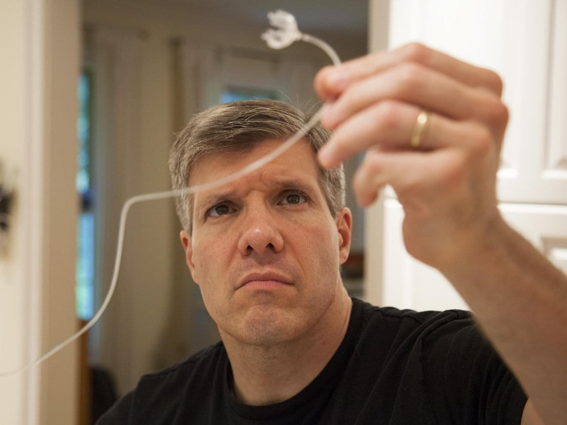 Ed tests tubing for his son's insulin pump.