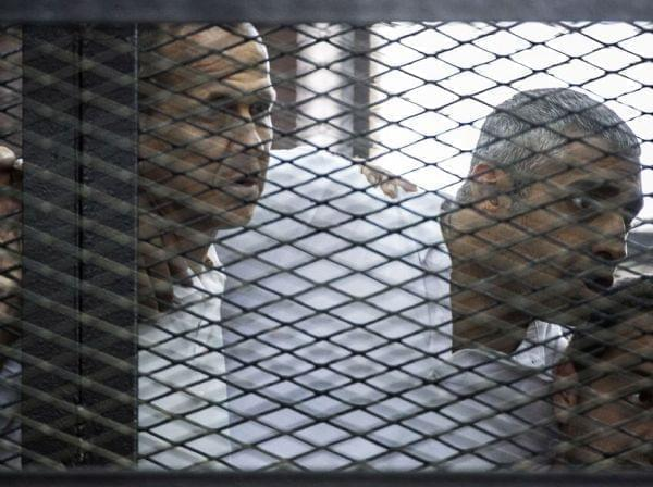 Al-Jazeera news channel's Australian journalist Peter Greste, left, and his colleagues, Egyptian-Canadian Mohamed Fadel Fahmy, center, and Egyptian Baher Mohamed listen to the verdict inside the defendants' cage during their trial for alleg