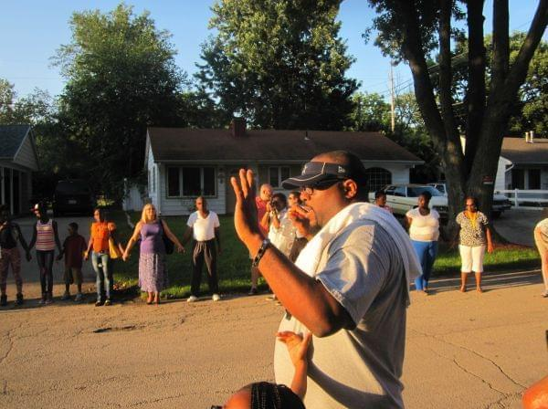 Rev. Lekevie Johnson of Jericho Missionary Baptist Church prays with about 100 participants gathered in a prayer circle during a community walk for peace in Champaign's Garden Hills neighborhood Wednesday evening.