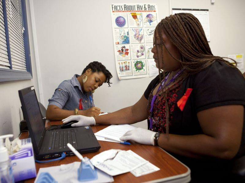 Katherine Tapp, 26, of New York City, left, fills out forms as Natrussa Williams, an HIV tester and counselor, waits for the results of Tapp's oral HIV test in southeast Washington, Wednesday, June 27, 2012.