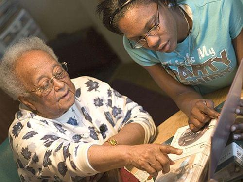 Erma Bridgewater shares family photos with Youth Media Workshop participant Amaris Bailey