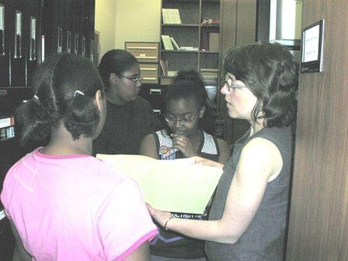 Youth Media Workshop students review documents at the Champaign County Historical Archives
