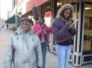 Erma Bridgewater walks through downtown Champaign with Youth Media Workshop students Isis Griffin and Amaris Bailey