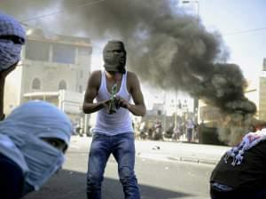 A Palestinian holds a Molotov cocktail during clashes with Israeli border police in Jerusalem on Wednesday, July 2, 2014.