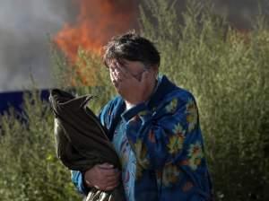 Woman cries near burning home in Slovyansk.