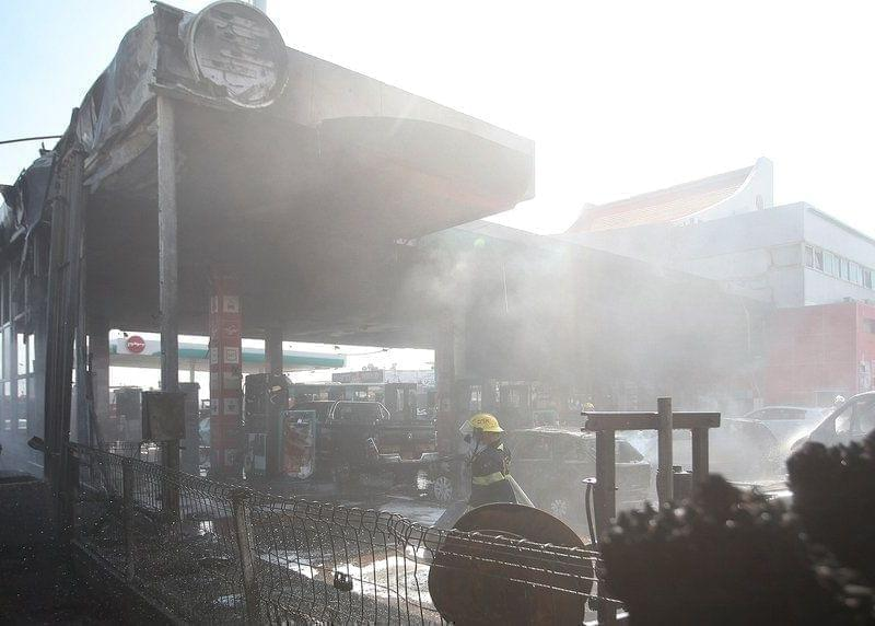 Israeli firefighters extinguish vehicles at a gas station hit by rocket fire.